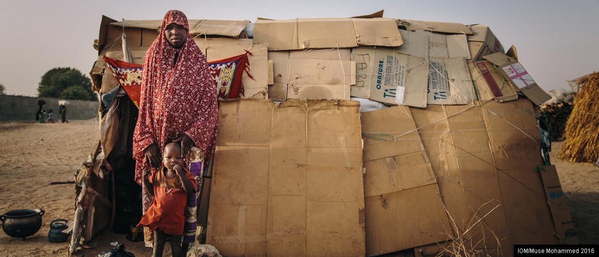 <br/>Maiduguri, Nigéria: une femme déplacée pose avec son fils devant un abri de fortune construit avec des cartons dans le camp de déplacés internes de Farm Center. Le camp, une ancienne usine de transformation, accueille désormais plusieurs milliers de personnes qui ont fui leurs villages principalement dans l'Etat de Borno. Certains déplacés vivent dans des abris d'urgence fournis par des organisations dont l'OIM. D'autres ont construit leur propre abri en utilisant les matériaux à leur disposition.