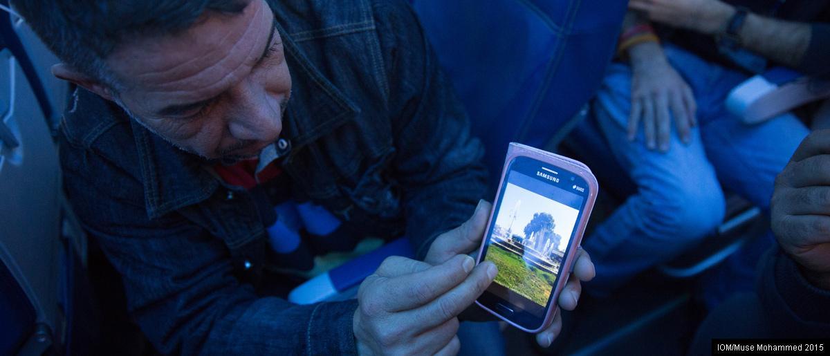 <br/>Quelque part au-dessus de l'Atlantique: un réfugié syrien en route vers sa nouvelle vie au Canada montre des photos de sa ville natale d'Hama sur son téléphone portable. Photo: OIM/Muse Mohammed
