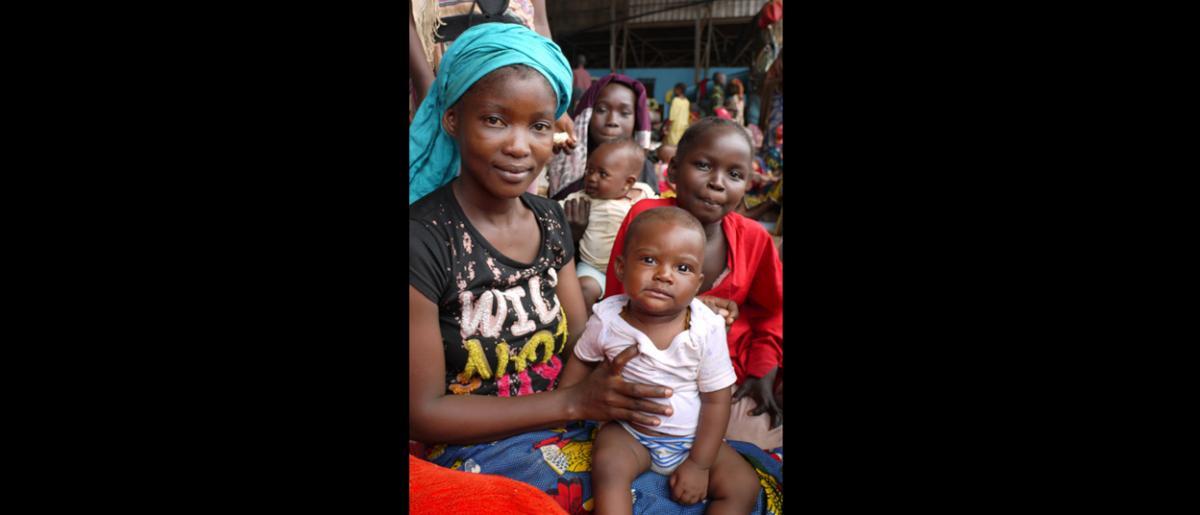 Une mère et son enfant au centre de transit de Bangui. Les 8 et 9 février, l'OIM a organisé deux vols charters qui ont permis d'évacuer 609 personnes vulnérables, dont des personnes âgées, de jeunes enfants et des personnes nécessitant des soins. Cependant, plus de 2 000 ressortissants de pays tiers se trouvent encore au centre de transit de l'aéroport militaire. © OIM 2014 (Photo de Sandra Black)