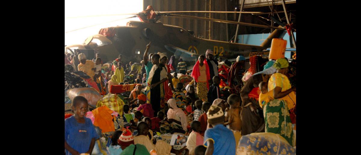 Installation de migrants dans des abris au centre de transit de l'aéroport militaire de Bangui (République centrafricaine). Les 8 et 9 février, l'OIM a organisé deux vols charters qui ont permis d'évacuer 609 personnes vulnérables, dont des personnes âgées, de jeunes enfants et des personnes nécessitant des soins. © OIM 2014 (Photo de François Goemans)