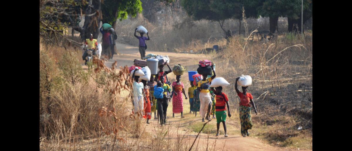 Un groupe de réfugiés traverse à pied la frontière séparant la RCA du Tchad, au village de Mini, près de Mbitoye (RCA). © OIM 2014 (Photo de Craig Murphy)