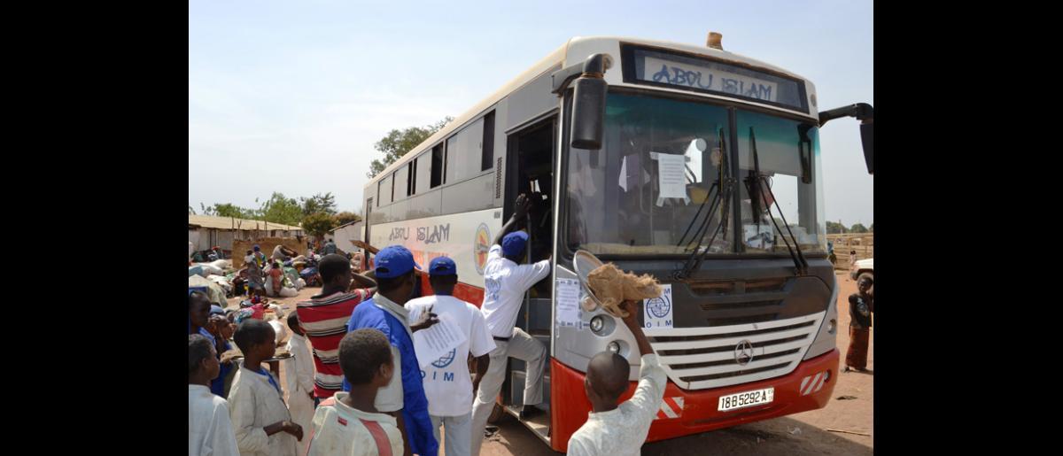 Un bus de l'OIM quittant la zone frontalière de Sido avec des Tchadiens de retour en route pour N'Djamena. © OIM 2014 (Photo de Craig Murphy)