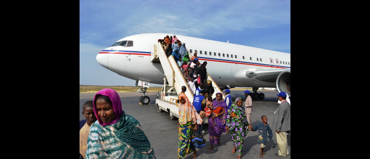 Un avion affrété par l'OIM arrive à N'Djamena avec des Tchadiens évacués de Bangui (RCA). © OIM 2014 (Photo de Craig Murphy)