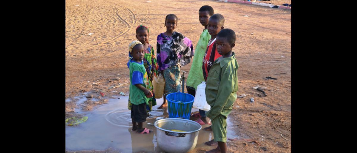 Enfants prenant de l'eau à un robinet au site de transit de Doba. © OIM 2014 (Photo de Craig Murphy)
