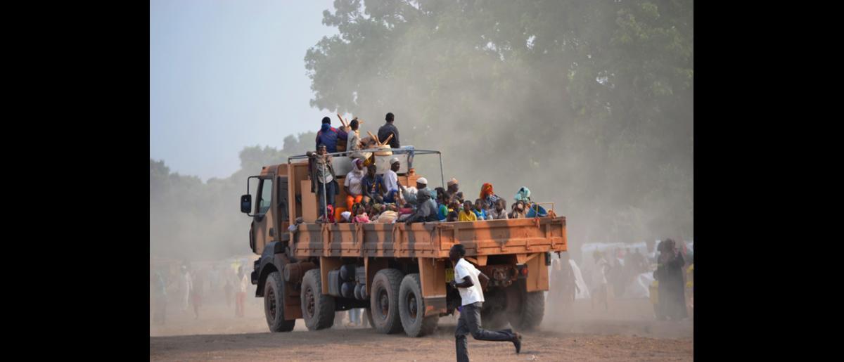 Important groupe de migrants de retour, comprenant un grand nombre de femmes et d'enfants, arrivant au centre de transit de Doyaba, à Sarh (Tchad). © OIM 2014 (Photo de Craig Murphy)