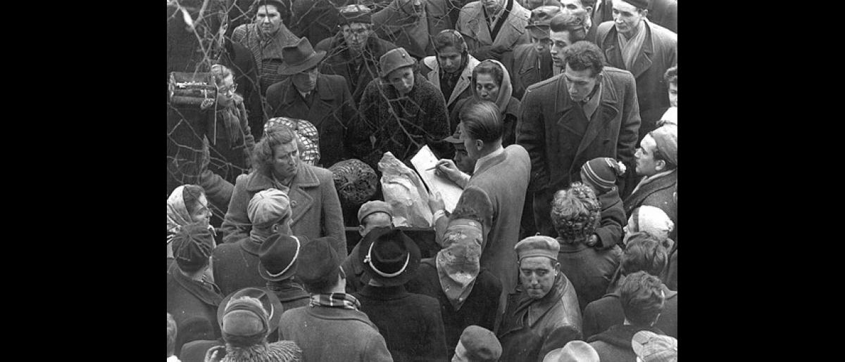 An ICEM staff member attempts to register a large crowd of Hungarian escapees before departure. Photo © Guy de Belleval 1958 – HAT0247