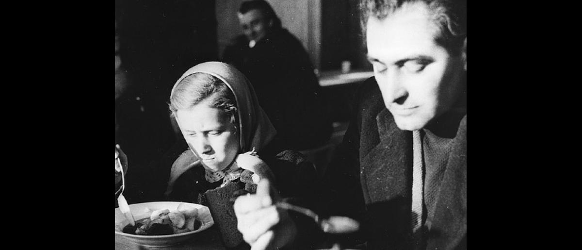 First meal for these Hungarian refugees after arriving at a camp in Austria. Photo © IOM 1956 – HAT0344