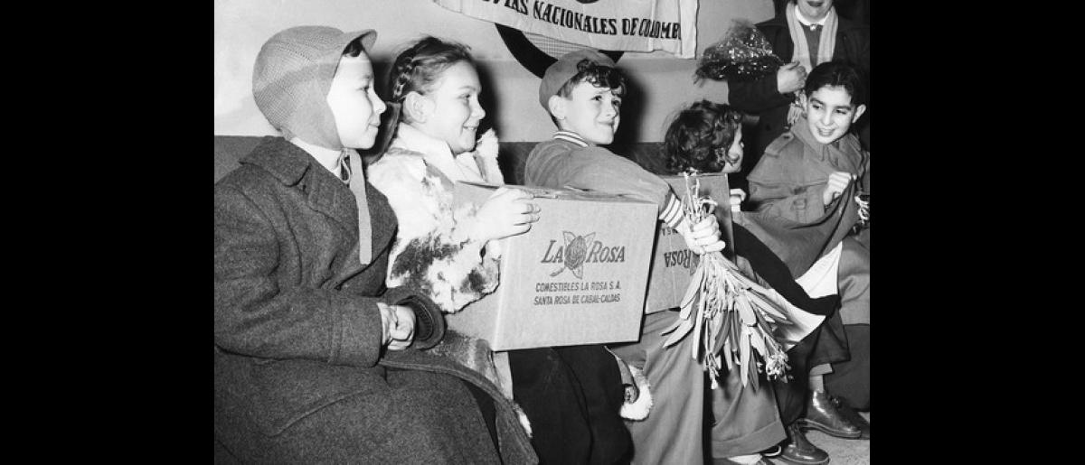 Hungarian children at Bogota's international airport are welcomed with gifts of chocolate from a local confectionary company. Photo © IOM 1957 – HCO0005