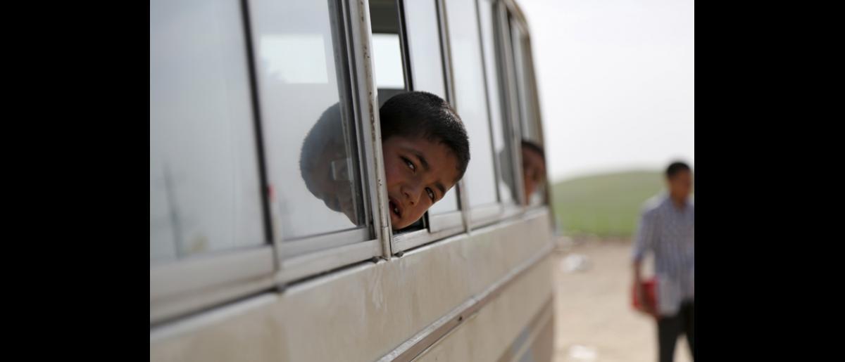 « Avant, mes enfants pleuraient parce qu'ils voulaient aller à l'école, mais c'était impossible », se lamente Sofiyah. « J'avais trop peur de les laisser partir seuls, à pied ». Cette mère de quatre enfants, originaire de Derik, dans le nord-est de la Syrie, dit qu'elle restait éveillée des nuits entières parce qu'elle se faisait du souci pour l'éducation de ses enfants. © OIM 2014