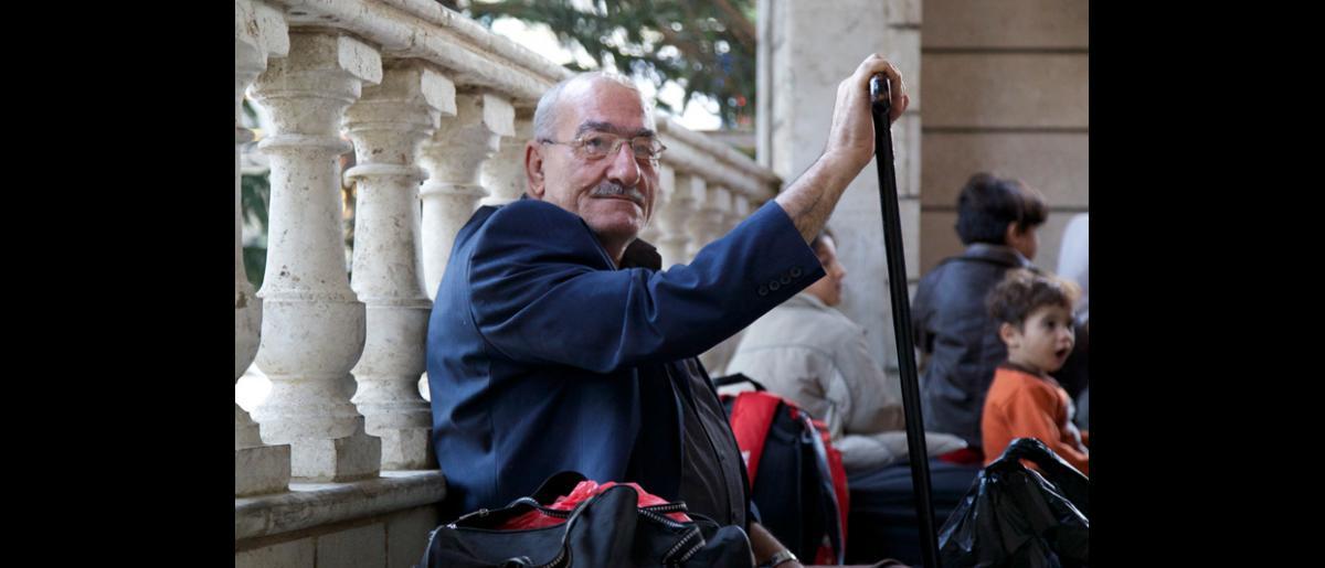 Un hombre espera pacientemente a que se pese su equipaje en la Oficina de la OIM en Beirut. El 10 de octubre de 2013, la Organización transportó a 106 refugiados sirios desde Beirut hasta Hanóver (Alemania). © OIM 2013 (Fotografía de Remi Itani)
