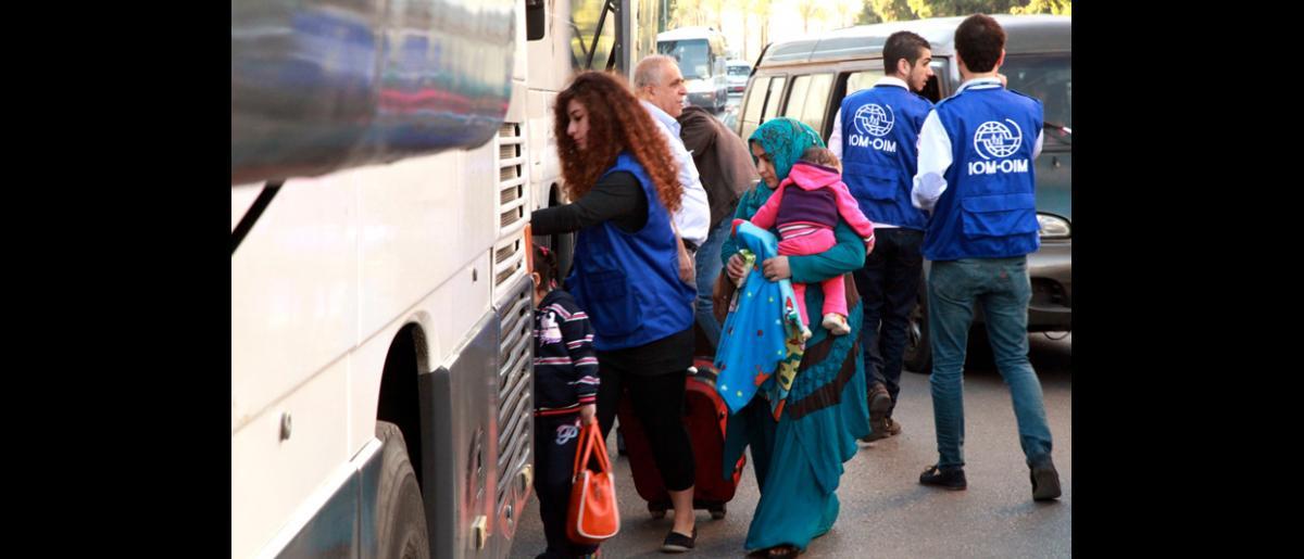 El personal de la OIM dio las últimas instrucciones a los refugiados que se preparaban para viajar en lo que fue el segundo vuelo de transporte de refugiados sirios a Alemania. © OIM 2013 (Fotografía de Remi Itani)