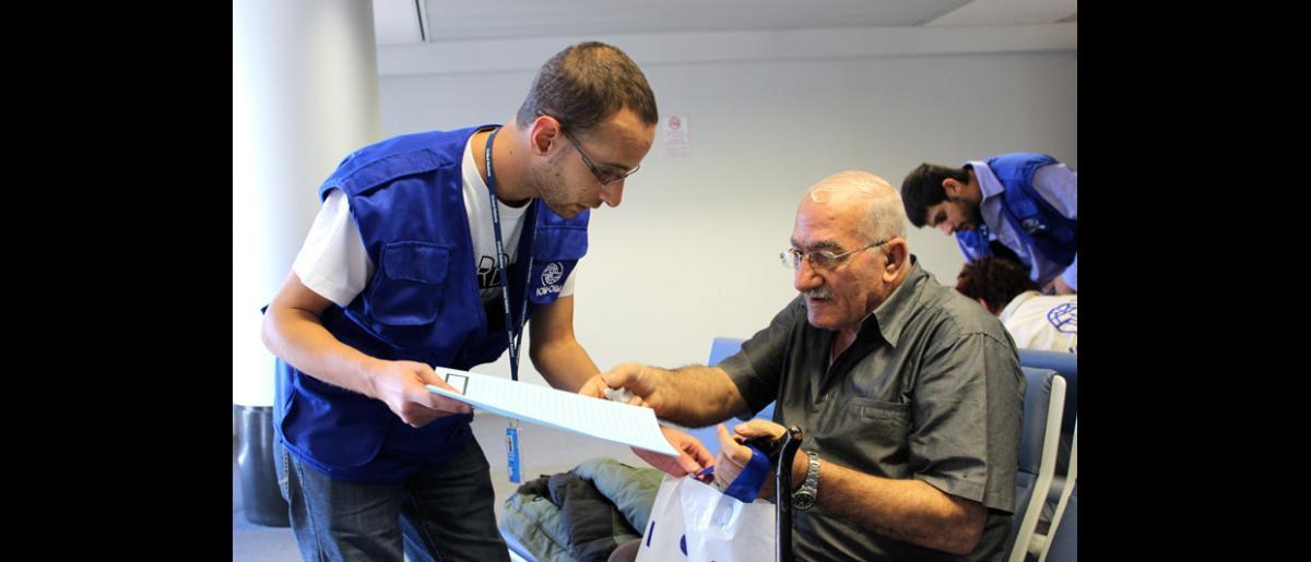 Un miembro del personal de la OIM entrega a un pasajero de edad avanzada una carpeta que contiene su salvoconducto alemán, así como información sobre sus derechos mientras resida en Alemania. © OIM 2013 (Fotografía de Samantha Donkin)