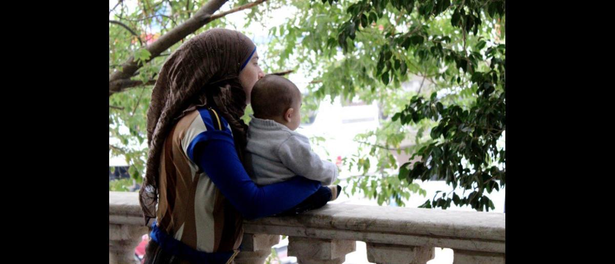 Una mujer y su hijo esperan pacientemente a ser llamados para subir al autobús que les llevará al aeropuerto. Éste será un largo día de viaje para algunos de los refugiados provenientes de la región septentrional del Líbano, que tuvieron que despertarse a las 3:00 de la mañana para llegar a Beirut al alba. © OIM 2013 (Fotografía por Samantha Donkin)