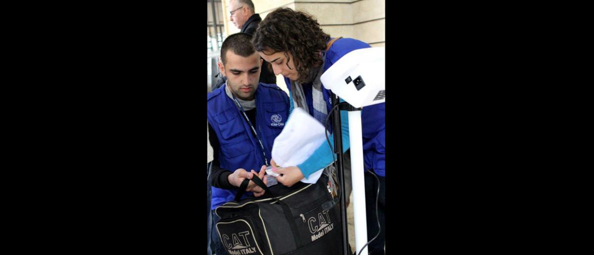 El personal de la OIM pesa y coloca etiquetas a todo el equipaje en la Oficina de la OIM en Beirut. © OIM 2013 (Fotografía por Samantha Donkin)