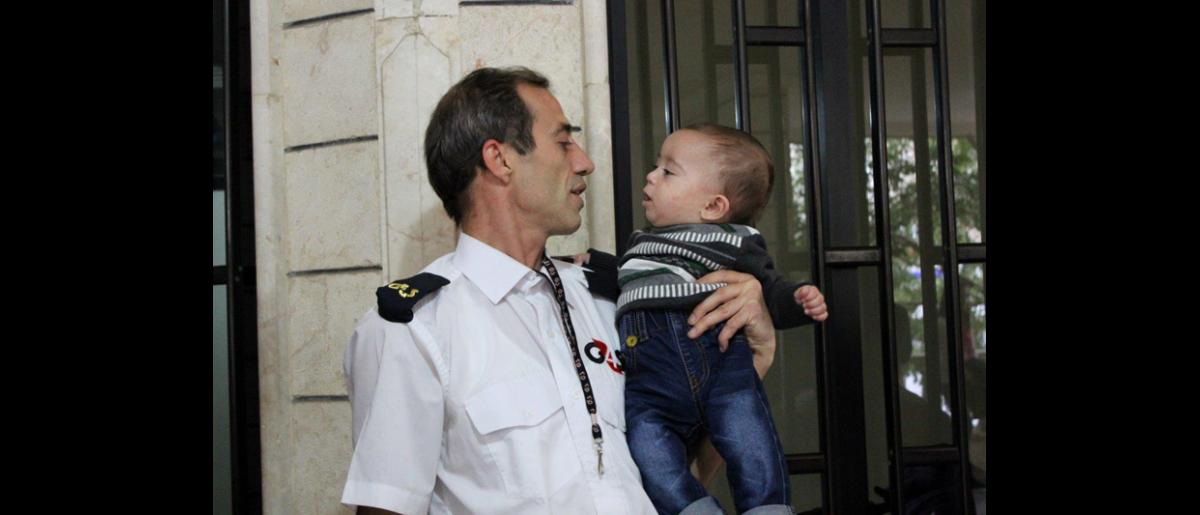 Un miembro del personal de seguridad de la OIM se despide de un bebé que ha conocido. El bebé, que nació en el Líbano, viajará a Alemania con sus padres, sus dos hermanos y sus tres hermanas. © OIM 2013 (Fotografía por Samantha Donkin)