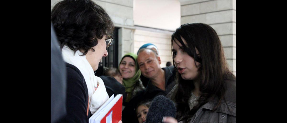 Los periodistas de la ARD entrevistan a una joven en la Oficina de la OIM en Beirut antes de que parta al aeropuerto. Viajará con sus padres y sus cinco hermanos, y esta noche llegarán al centro de acogida establecido en Friedland. © OIM 2013 (Fotografía por Samantha Donkin)