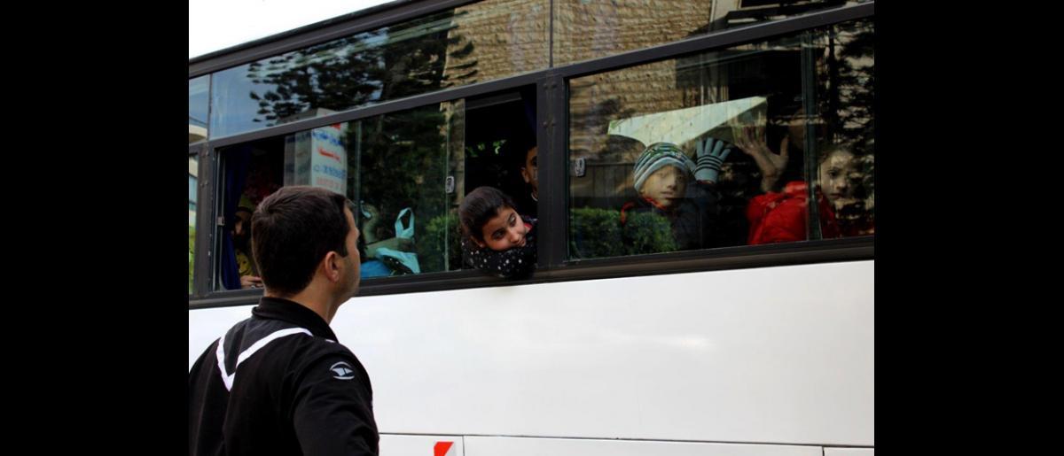 Es un día emocionante pero triste para muchos refugiados que viajarán a Alemania, ya que dejan atrás a familiares sin saber cuándo volverán a verlos. © OIM 2013 (Fotografía por Samantha Donkin)