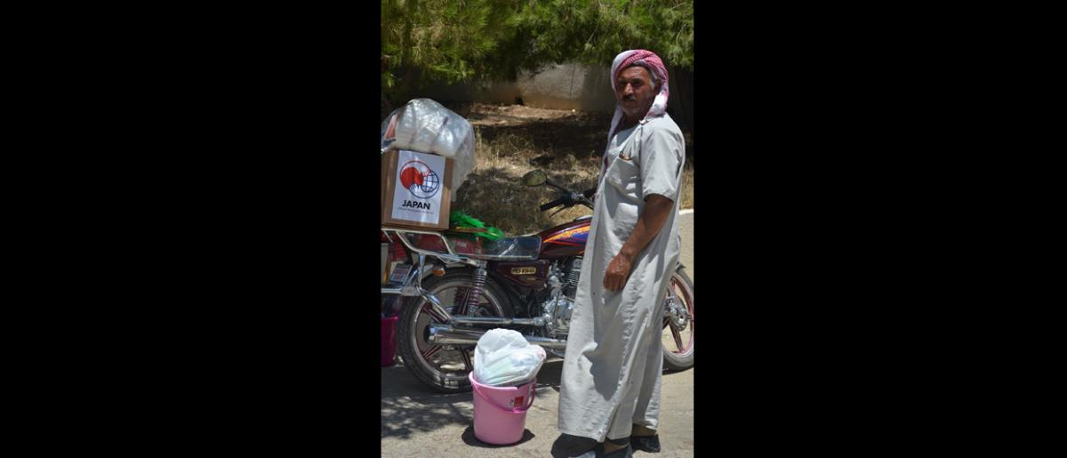 A Syrian refugee loads NFIs onto the back of his motorbike at a distribution site in Ansariyeh Municipality. IOM distributed essential household items to vulnerable Syrian families that are in living in derelict buildings or rented accommodation in the area.