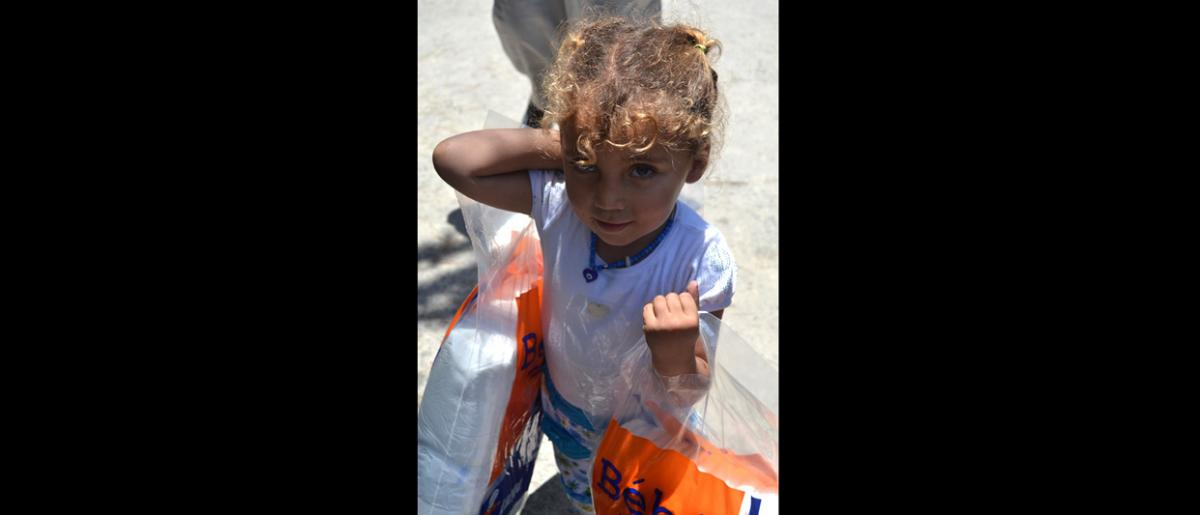 Une petite fille porte un paquet de couches provenant d'une distribution d'articles non alimentaires dans la municipalité d'Ansariyeh. Le Liban accueille plus 500 000 réfugiés syriens enregistrés, dont plus de la moitié a moins de 18 ans. © OIM 2013 (Photo : Fouad Al Sayed)