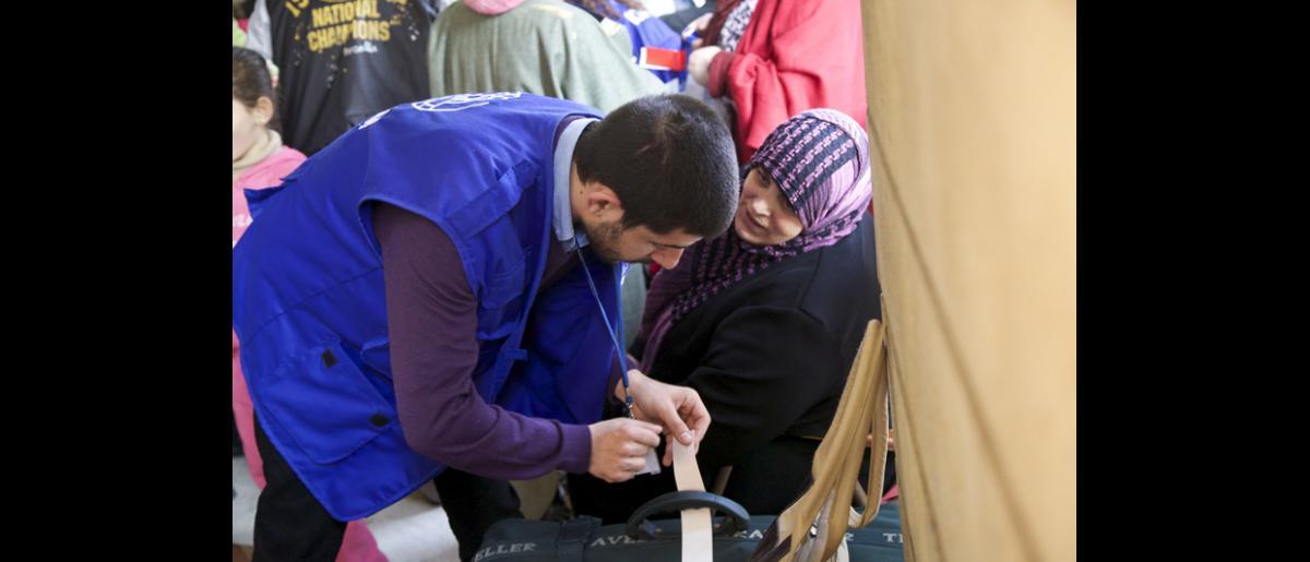 Un membre du personnel de l'OIM chargé des opérations étiquette les bagages des passagers pendant l'embarquement. Le 18 février, l'OIM a aidé 159 adultes, 74 enfants et 12 nourrissons à s'envoler pour Hanovre (Allemagne) depuis Beyrouth (Liban). © OIM 2014 (Photo : Remi Itani)