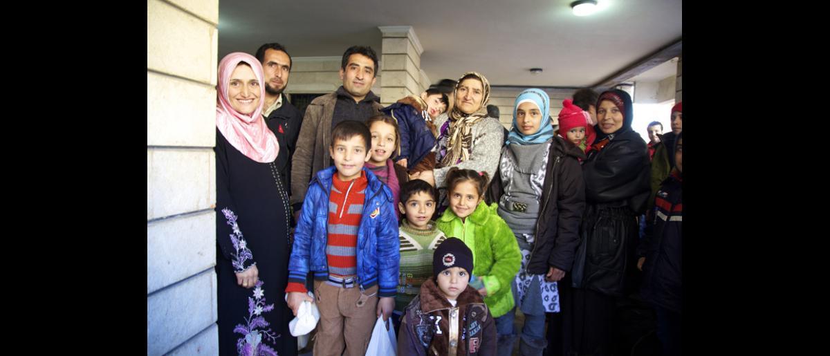 Ultime photo de famille pour des Syriens qui ignorent quand ils seront à nouveau réunis. © OIM 2014 (Photo : Remi Itani)