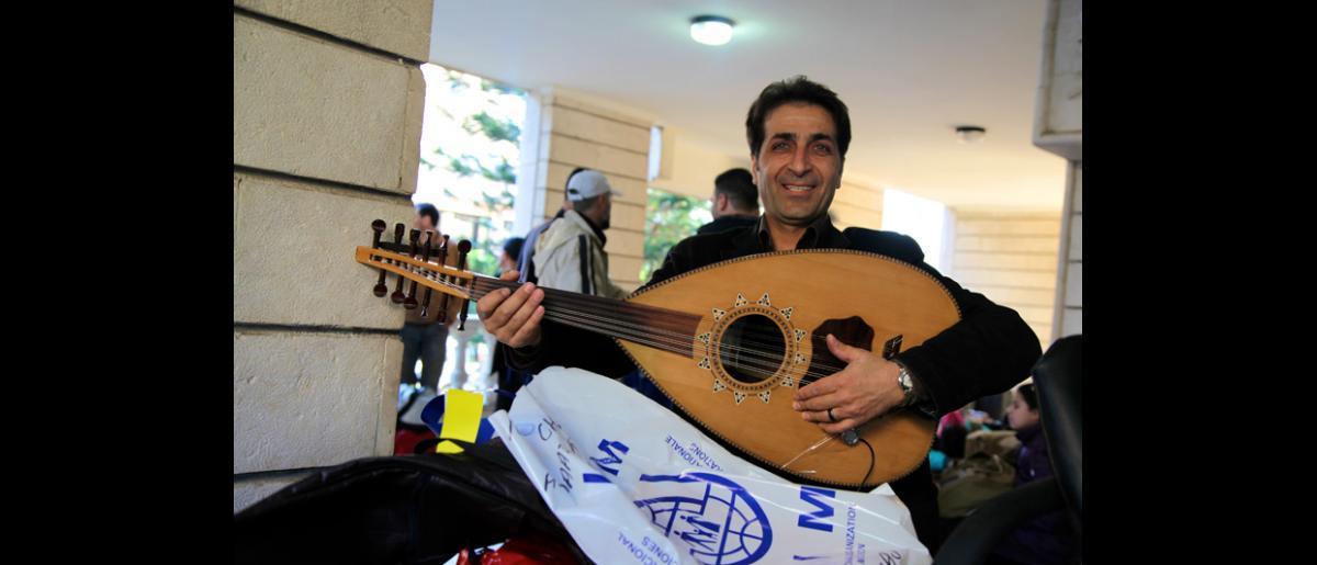 Cet homme, qui quitte la Syrie avec sa femme, son fils et sa fille, n'a pas oublié de prendre avec lui son bien le plus précieux, un oud, un instrument de musique traditionnel qui lui rappellera son pays. © OIM 2014 (Photo : Remi Itani)