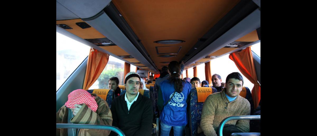 Des accompagnateurs de l'OIM comptent les passagers avant le départ pour l'aéroport. Ceux ci ont droit à 20 kilos de bagage au plus chacun, une contrainte difficile à respecter pour certains. © OIM 2014 (Photo : Remi Itani)