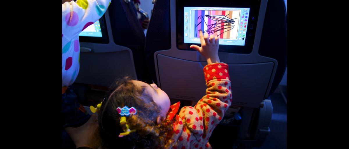 Dans l'avion, des enfants s'amusent avec le système de divertissement en vol d'AirBerlin pendant que leurs parents se reposent. © OIM 2014 (Photo : Remi Itani)