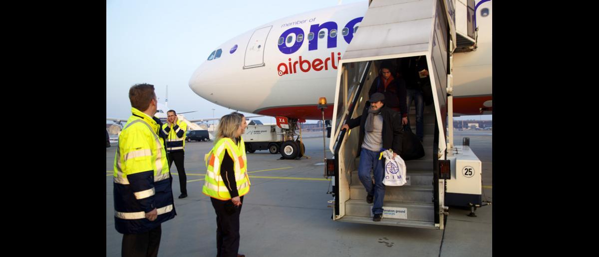 Des réfugiés syriens arrivant à l'aéroport international d'Hanovre au terme d'un long voyage qui a duré trois heures. Les rigueurs de l'hiver européen les ont obligés à s'habiller chaudement. © OIM 2014 (Photo : Remi Itani)