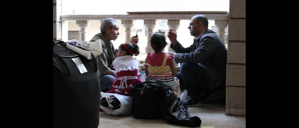 Dos hombres charlan tranquilamente en un rincón del patio de la Oficina de la OIM en Beirut. El 11 de septiembre pasado, 107 refugiados sirios embarcaron en un avión en Beirut (Líbano), que aterrizó por la tarde en Hanóver (Alemania). © OIM 2013 (Fotografía de Samantha Donkin)