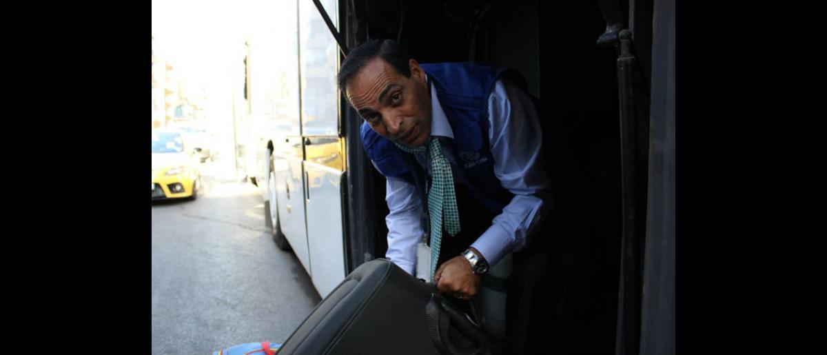 Todos ponen manos a la obra. El Jefe de la Oficina de la OIM en el Líbano, Fawzi Alzioud, carga el equipaje en los autobuses que conducirán a los refugiados al aeropuerto. © OIM 2013 (Fotografía de Samantha Donkin)