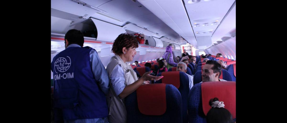 Rana Jaber, responsable del programa, charla con los pasajeros antes del despegue. © OIM 2013 (Fotografía de Samantha Donkin)