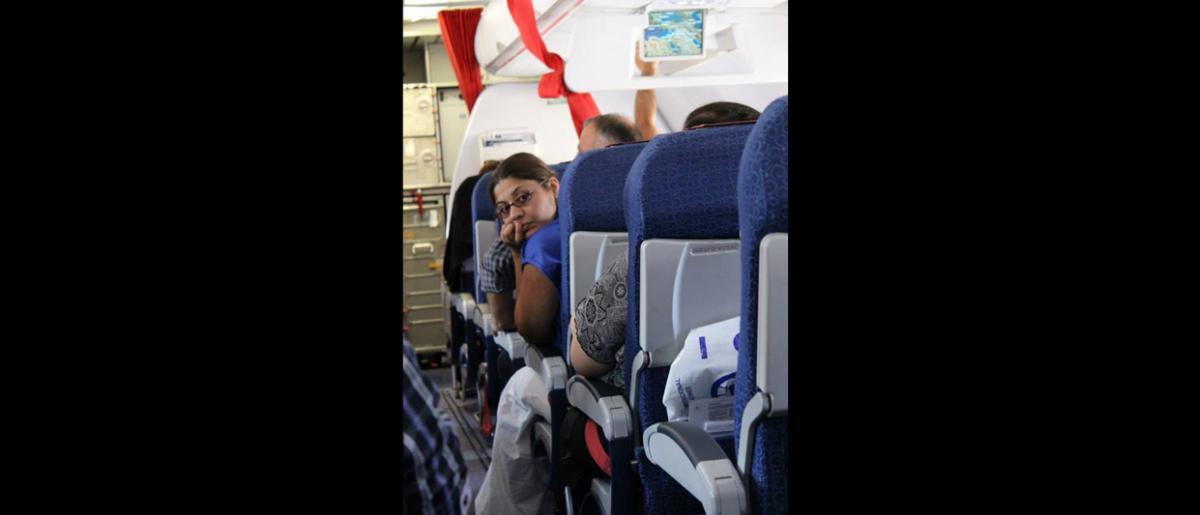 La Dra. Ramona es la acompañante médica de un paciente que padece epilepsia. El cometido de los acompañantes médicos durante el vuelo es cuidar de los beneficiarios del programa que tienen problemas de salud. © OIM 2013 (Fotografía de Samantha Donkin)