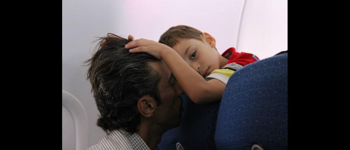 Muchas familias madrugaron para poder llegar a la Oficina de la OIM antes de las 7 de la mañana. Cuando el grupo embarcó en el avión, la mayoría de los niños mostraban signos de fatiga. © OIM 2013 (Fotografía de Samantha Donkin)