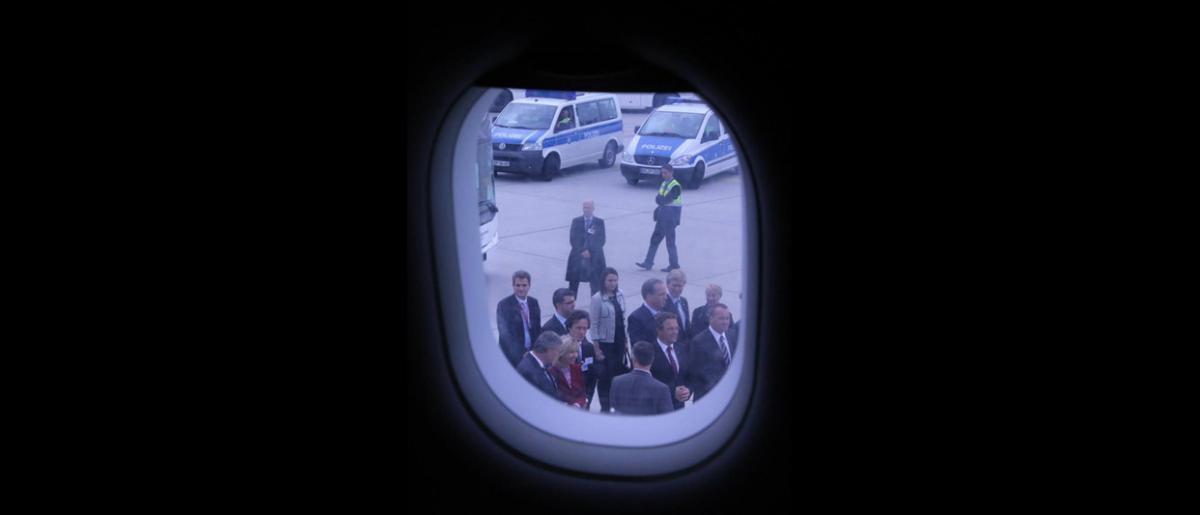 El avión se detiene cerca de la terminal, donde un comité de bienvenida se dispone a recibir a los refugiados sirios provenientes del Líbano. © OIM 2013 (Fotografía de Samantha Donkin)