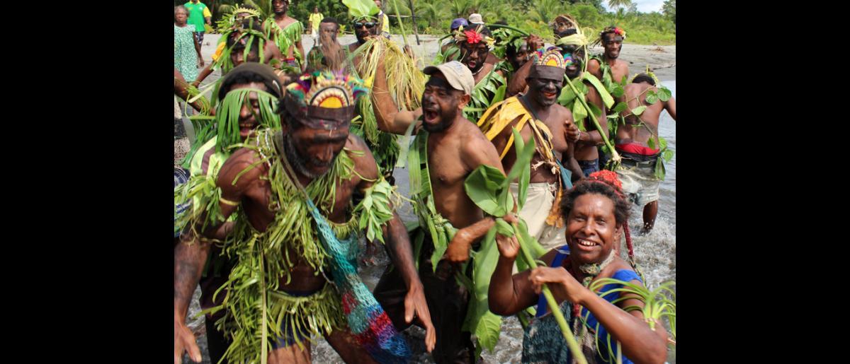 Accueil traditionnel dans le village de Labu Tale, dans le nord de la Papouasie-Nouvelle- Guinée, lors de la visite effectuée par la délégation de l'OIM. © OIM 2014 (Photo de Joe Lowry)