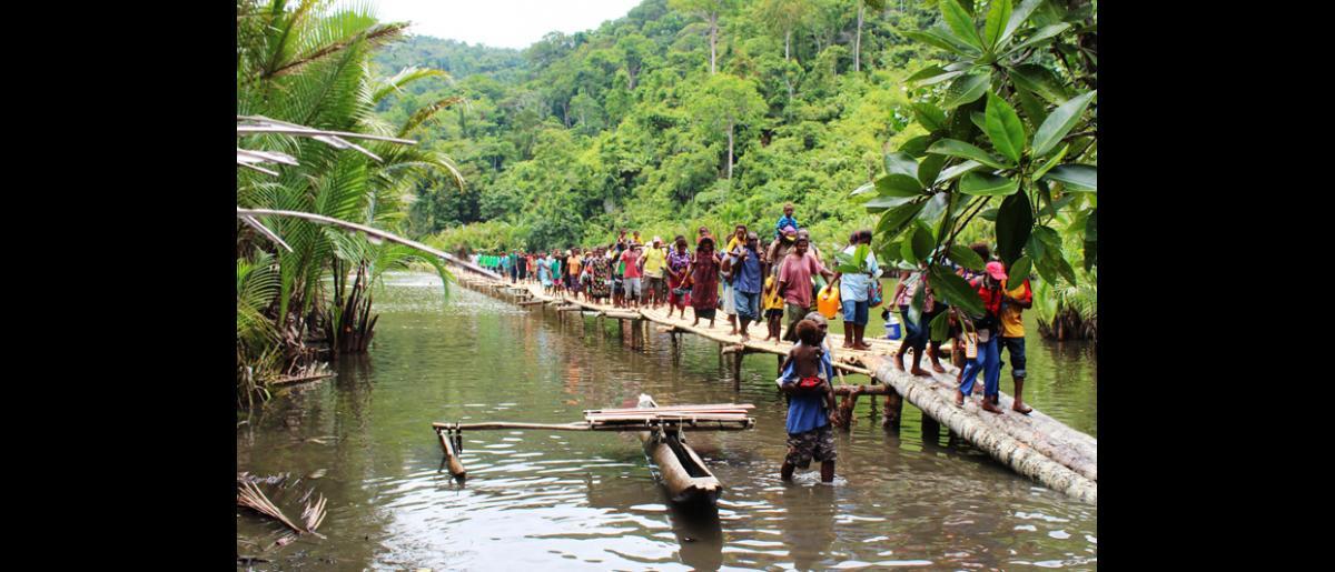 Villageois empruntant un pont de secours lors de manœuvres d'entraînement aux catastrophes, dans un village isolé de Papouasie-Nouvelle-Guinée. Ce pont a été construit avec des matériaux locaux par de la main d'œuvre locale dans le cadre d'un programme de gestion des risques de catastrophe à l'échelle locale mis en œuvre par l'OIM dans le village de Labu Tale. © OIM 2014 (Photo de Joe Lowry)