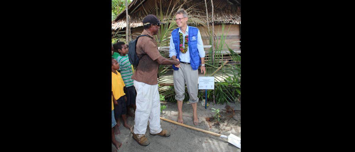 Le Directeur régional pour l'Asie et le Pacifique, Andrew Bruce, est félicité par un habitant au moment de planter un arbre pour célébrer le lancement du programme de gestion des risques de catastrophe à l'échelle locale, à Labu Tale, un village isolé du nord de la Papouasie-Nouvelle-Guinée. © OIM 2014 (Photo de Joe Lowry)