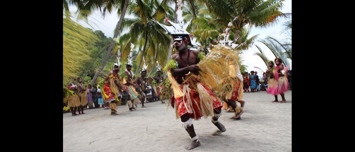 Un danseur guerrier de Labu Tale, un village isolé du nord de la Papouasie-Nouvelle-Guinée, participe à une cérémonie organisée pour célébrer la réussite du programme OIM/USAID de gestion des risques de catastrophe à l'échelle locale. © OIM 2014 (Photo de Joe Lowry)