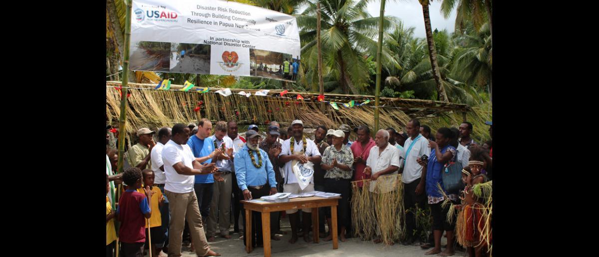 Au centre de la photo, le Directeur régional pour l'Asie et le Pacifique, Andrew Bruce, le Chef de mission, George Gigauri, et le Chef suprême, Aron Aima BEM, signent un document marquant la deuxième phase d'un programme de gestion des risques de catastrophe à l'échelle locale, mené avec succès par l'OIM et USAID à Labu Tale, dans le nord de la Papouasie-Nouvelle-Guinée. © OIM 2014 (Photo de Joe Lowry)