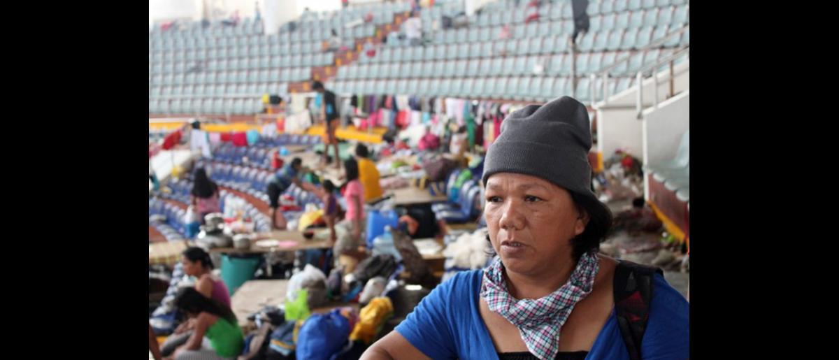 """Ophelia Casio, una viuda de 46 años de edad y madre de ocho hijos, perdió su hogar y todas sus pertenencias como consecuencia del tifón y ahora se encuentra en el centro de refugio """"Astrodome"""" de Tacloban, donde fue reclutada como voluntaria para recabar datos que serán incorporados en la Matriz de Seguimiento de los Desplazamientos. © OIM 2013 (Fotografía de Joe Lowry)"""