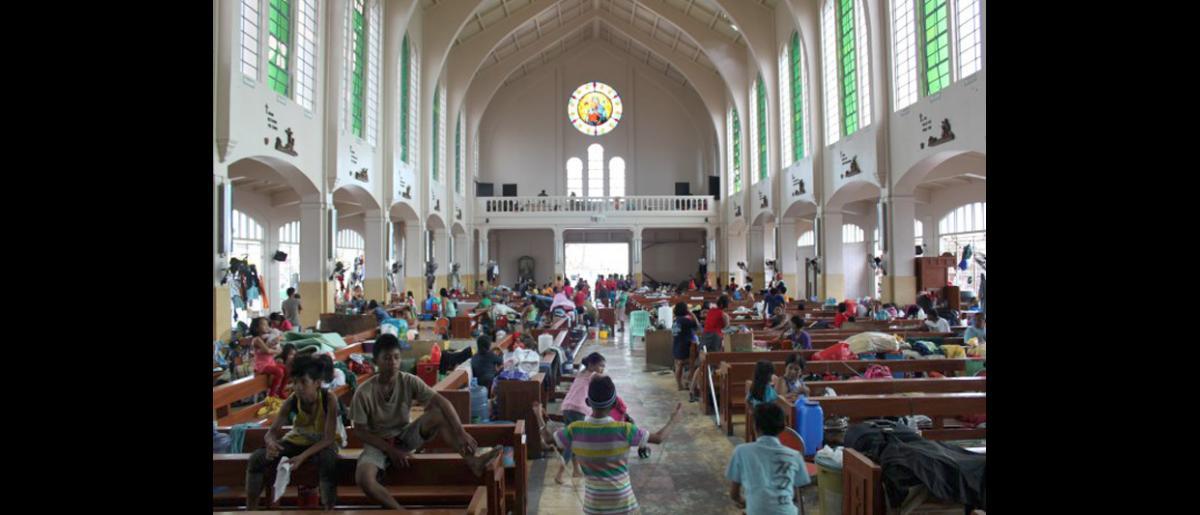 La iglesia redentorista de la ciudad de Tacloban, se ha convertido en un centro de refugio para varios cientos de desplazados. © OIM 2013 (Fotografía de Joe Lowry)