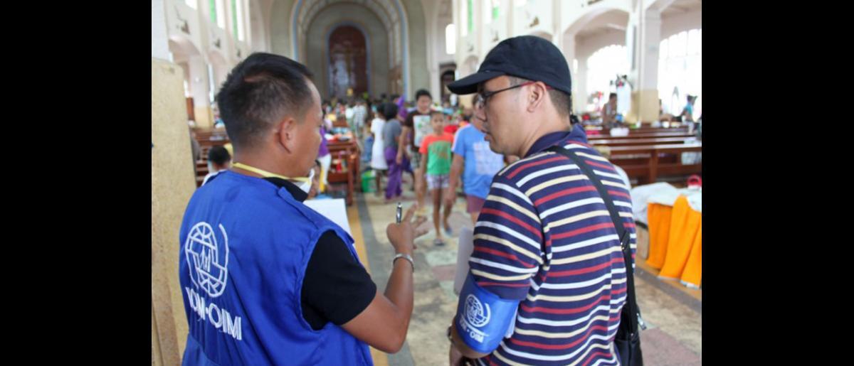 Jury Dos Santos y Mark Maulit, encargados de la gestión y la coordinación de campamentos de la OIM, en la iglesia redentorista de la ciudad de Tacloban —que se ha convertido en un centro de refugio para varios cientos de desplazados— han reclutado a voluntarios de la población desplazada para que recaben datos que serán incorporados en la Matriz de Seguimiento de los Desplazamientos de la OIM. © OIM 2013 (Fotografía de Joe Lowry)
