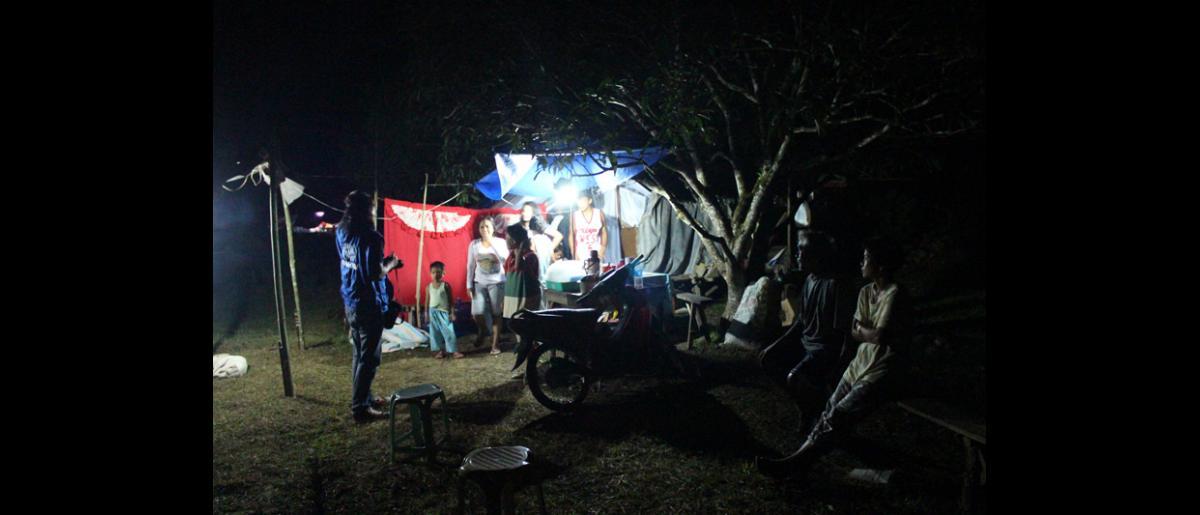 """""""Resiliencia al estilo filipino"""": así es como Lionel Dosdos, de la OIM (a la izquierda), califica la actitud positiva de los 16 miembros de las familias Simbahon y Atabelo (de edades comprendidas entre los 4 y los 87 años), que duermen en la misma tienda de campaña. Ramón Atabelo (segundo empezando por la derecha) nos dice: """"Estamos apretados como sardinas en lata"""". © OIM 2013 (Fotografía de Joe Lowry)"""