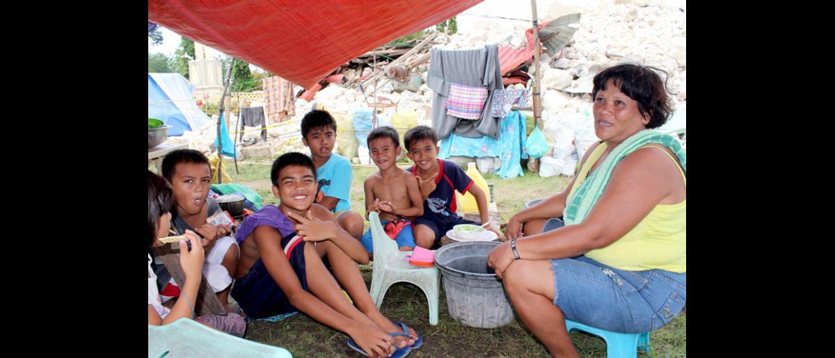 """Rosario Mejares, de 42 años de edad, y algunos de sus familiares, se encuentran en el centro de desplazados, establecido en los terrenos de la iglesia en ruinas en Loon, Bohol. Rosario nos dice: """"Sobre todo necesitamos letrinas, porque estamos lejos de nuestras casas y algunas veces tenemos que salir corriendo. Además los niños se están enfermando, las fuentes de agua se encuentran demasiado lejos, y los precios de los alimentos se han duplicado desde el terremoto."""" © OIM 2013 (Fotografía de Joe Lowry)"""