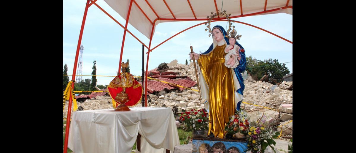 Un santuario improvisado para rendir culto a Nuestra Señora de la Luz, la única estatua que quedó intacta tras el terremoto de magnitud 7,2 que destruyó la iglesia construida alrededor de 1850 en Loon. © OIM 2013 (Fotografía de Joe Lowry)