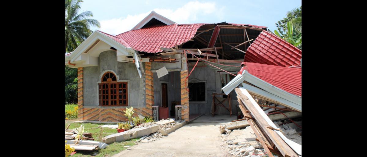 Casa dañada por el terremoto en las inmediaciones de Maribojoc, Bohol, en la región central de Filipinas. © OIM 2013 (Fotografía de Joe Lowry)