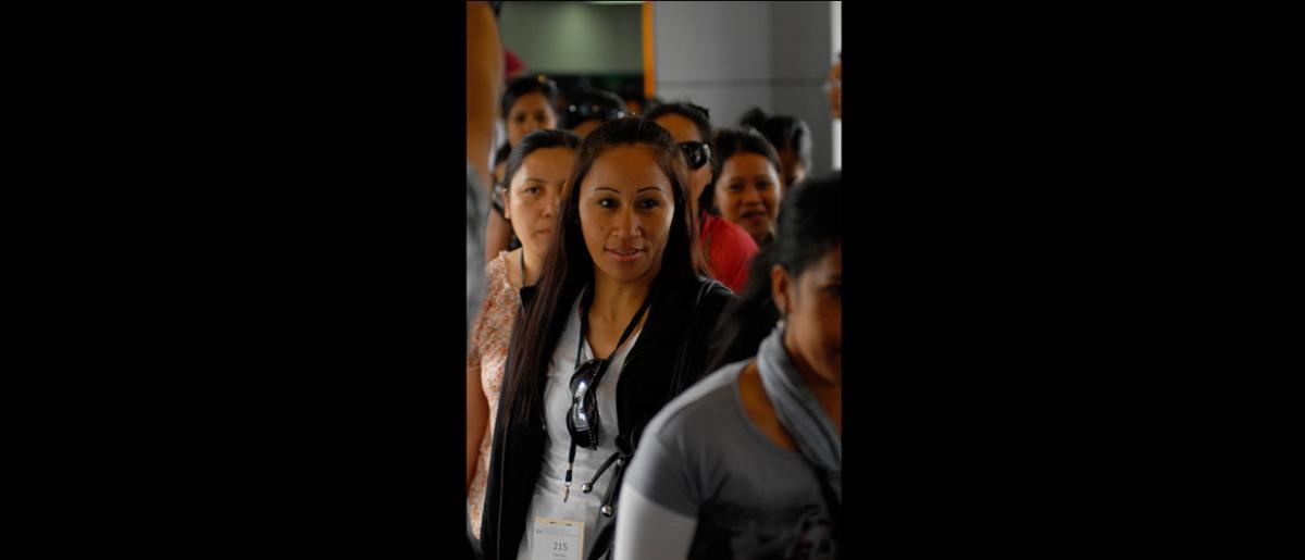 Nacionales filipinos a su llegada a Manila, el 11 de septiembre, tras partir de Damasco (Siria), en un vuelo fletado por la Organización.   En la imagen, Avegail Cruz (derecha), de la OIM, entrevista a una de las personas retornadas. © OIM 2012 (Foto: Ray Leyesa)