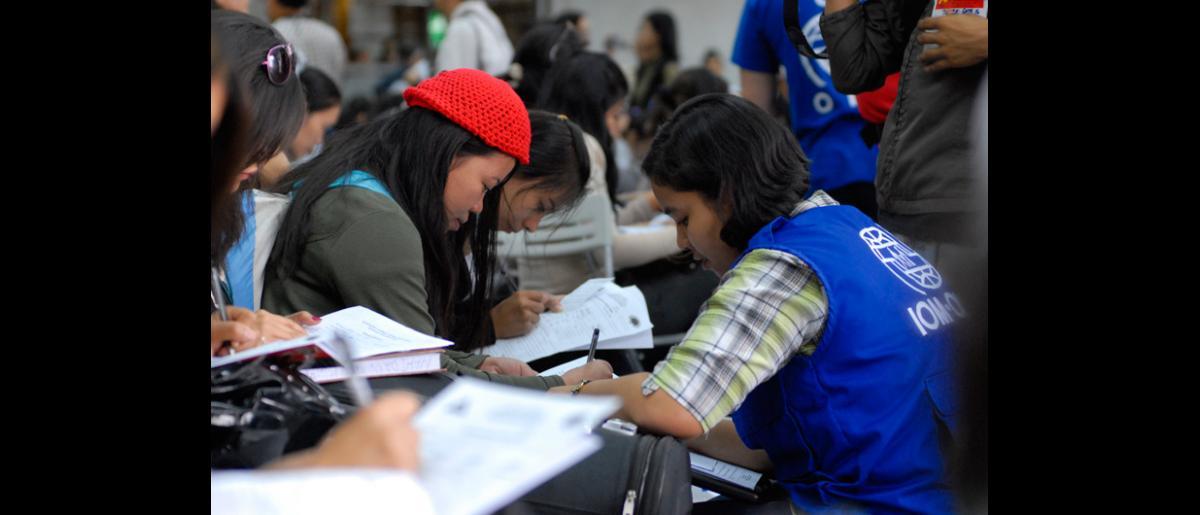 Filipinos rellenan los formularios pertinentes al llegar a Manila, el 11 de septiembre, tras partir de Damasco.  La OIM se ocupó de la operación de traslado aéreo. © OIM 2012 (Foto: Ray Leyesa)