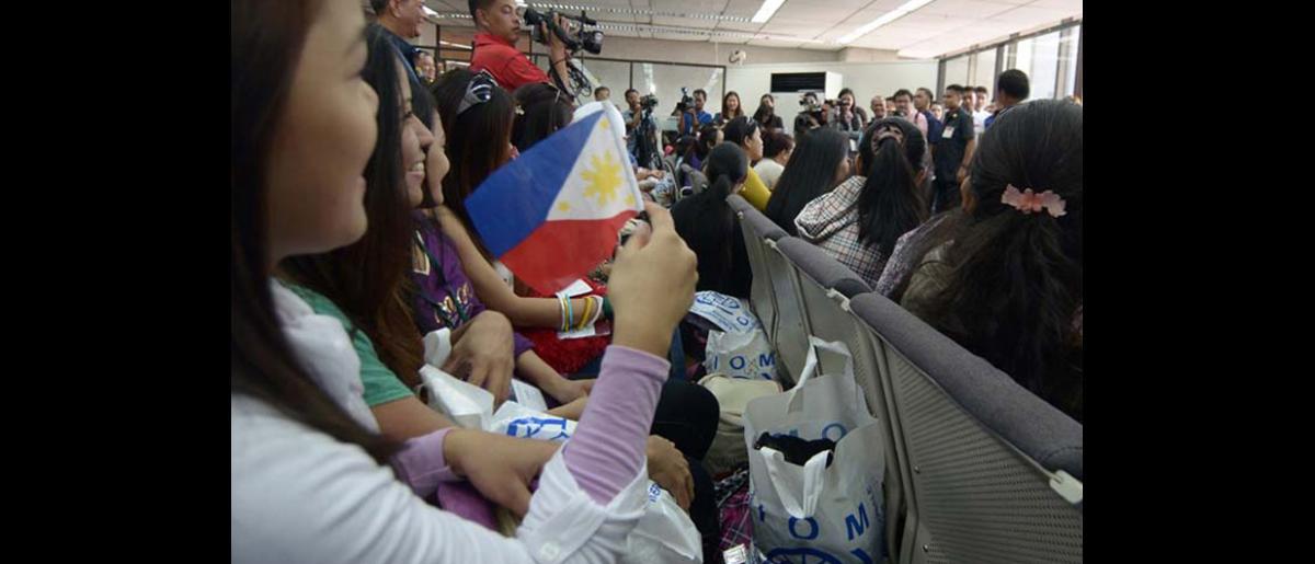 Los retornados saludan y expresan sus sentimientos a los medios de comunicación locales a su llegada a Manila. © OIM 2012 (Foto: Ray Leyesa)